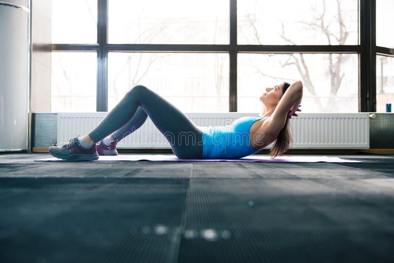 Νέα γυναίκα που βρίσκεται στο χαλί γιόγκας και που κάνει την άσκηση ικανότητας στοκ εικόνα με δικαίωμα ελεύθερης χρήσης