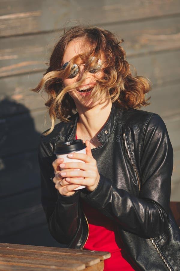 Νέα γυναίκα που γελά στα στρογγυλά γυαλιά και έναν μαύρο καφέ κατανάλωσης σακακιών δέρματος στοκ φωτογραφίες με δικαίωμα ελεύθερης χρήσης