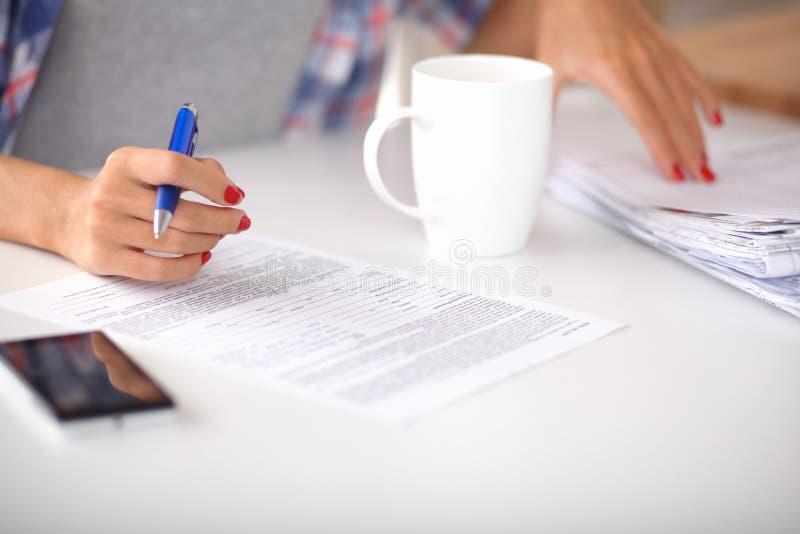 Νέα γυναίκα που γράφει κάτι στο σημειωματάριό της στοκ εικόνες