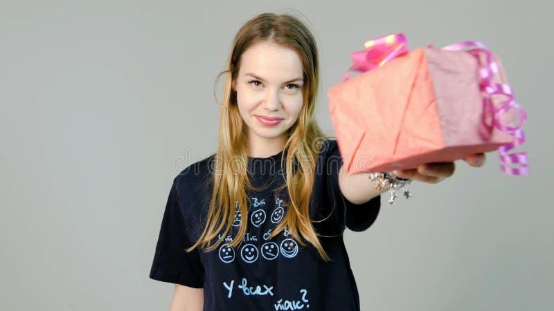 Νέα γυναίκα που δίνει ένα δώρο σε ένα άσπρο υπόβαθρο Νέα γυναίκα που δίνει ένα δώρο στη κάμερα στοκ εικόνες με δικαίωμα ελεύθερης χρήσης
