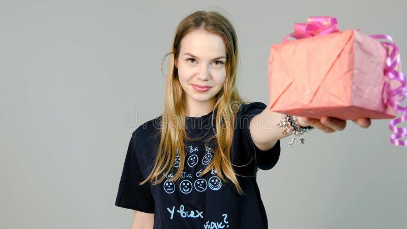 Νέα γυναίκα που δίνει ένα δώρο σε ένα άσπρο υπόβαθρο Νέα γυναίκα που δίνει ένα δώρο στη κάμερα στοκ εικόνα με δικαίωμα ελεύθερης χρήσης