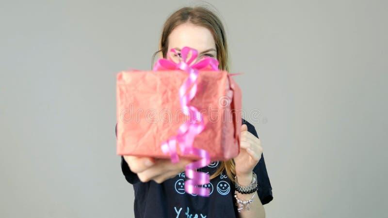 Νέα γυναίκα που δίνει ένα δώρο σε ένα άσπρο υπόβαθρο Νέα γυναίκα που δίνει ένα δώρο στη κάμερα στοκ εικόνα
