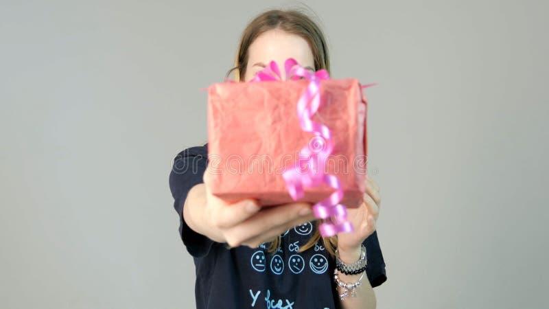 Νέα γυναίκα που δίνει ένα δώρο σε ένα άσπρο υπόβαθρο Νέα γυναίκα που δίνει ένα δώρο στη κάμερα στοκ εικόνες