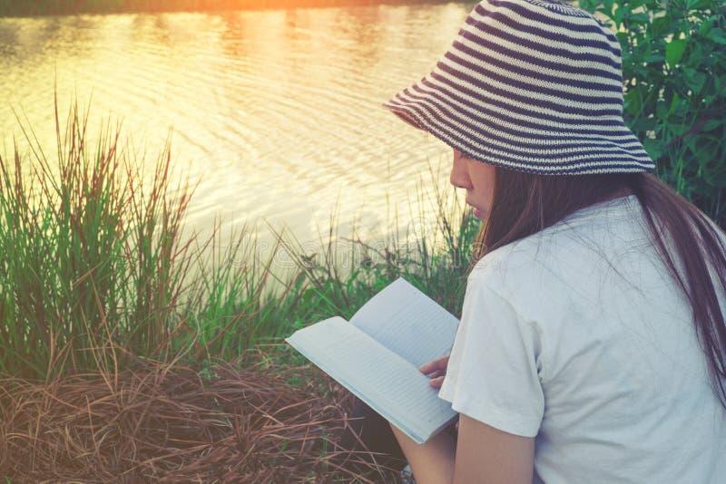 Νέα γυναίκα που διαβάζει ένα βιβλίο που βρίσκεται στη χαλάρωση στο πάρκο στοκ φωτογραφίες