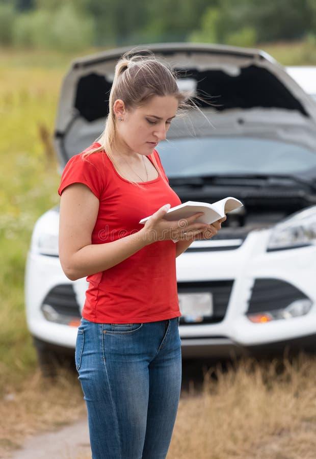 Νέα γυναίκα που διαβάζει το χειρωνακτικό βιβλίο για το σπασμένο αυτοκίνητό της στοκ φωτογραφία με δικαίωμα ελεύθερης χρήσης