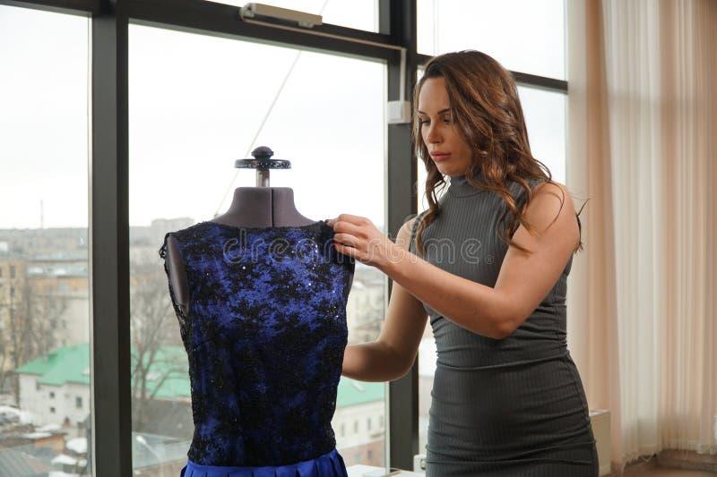 Νέα γυναίκα που δοκιμάζει ένα φόρεμα σε ένα μανεκέν, μοδίστρα στο εργαστήριο στοκ εικόνα με δικαίωμα ελεύθερης χρήσης