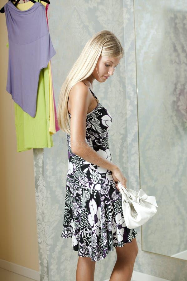 Νέα γυναίκα που δοκιμάζει το φόρεμα επάνω στοκ εικόνες με δικαίωμα ελεύθερης χρήσης