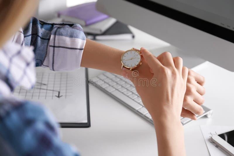 Νέα γυναίκα που ελέγχει το χρόνο στο wristwatch της στοκ εικόνες