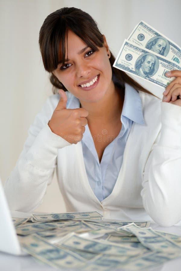Νέα γυναίκα που εξετάζει σας δολάρια μετρητών εκμετάλλευσης στοκ εικόνες