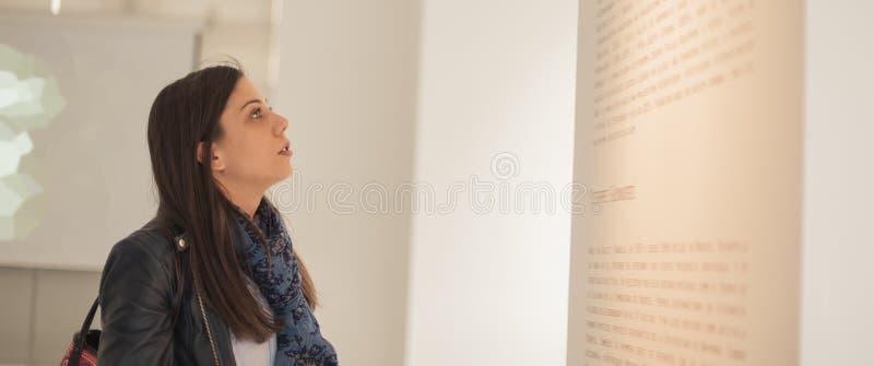 Νέα γυναίκα που εξετάζει τη σύγχρονη ζωγραφική στο γκαλερί τέχνης στοκ εικόνες με δικαίωμα ελεύθερης χρήσης