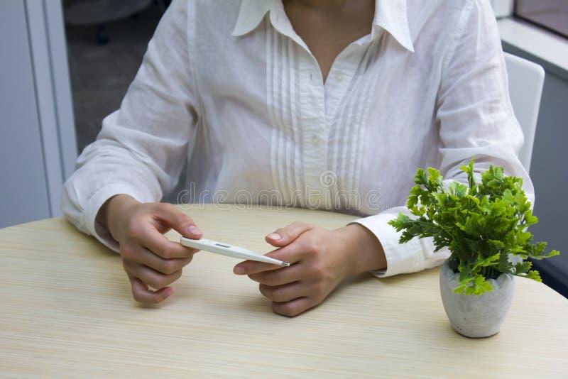 Νέα γυναίκα που εξετάζει το θερμόμετρο στοκ φωτογραφία με δικαίωμα ελεύθερης χρήσης