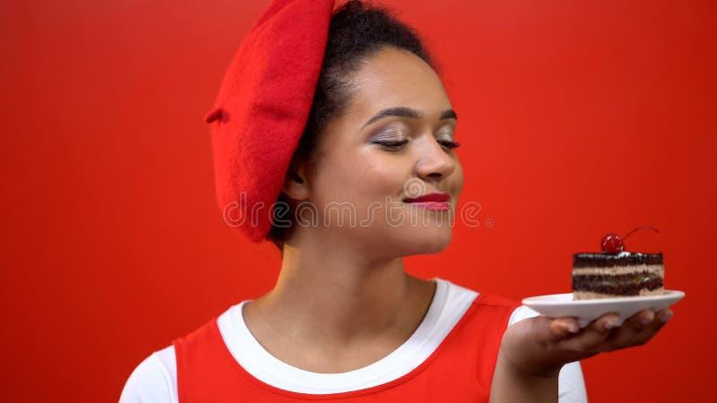 Νέα γυναίκα που εξετάζει το νόστιμο κέικ σοκολάτας με το κόκκινο κεράσι, ευχαρίστηση επιδορπίων στοκ εικόνα