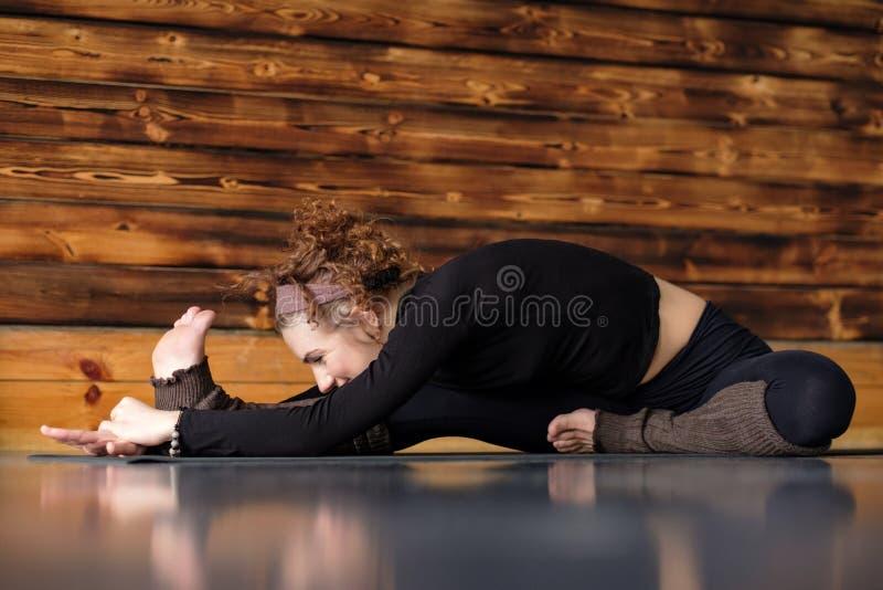 Νέα γυναίκα που επιλύει κάνοντας τη συνεδρίαση γιόγκας ή pilates άσκησης σε Janu Sirsasana στοκ φωτογραφία με δικαίωμα ελεύθερης χρήσης