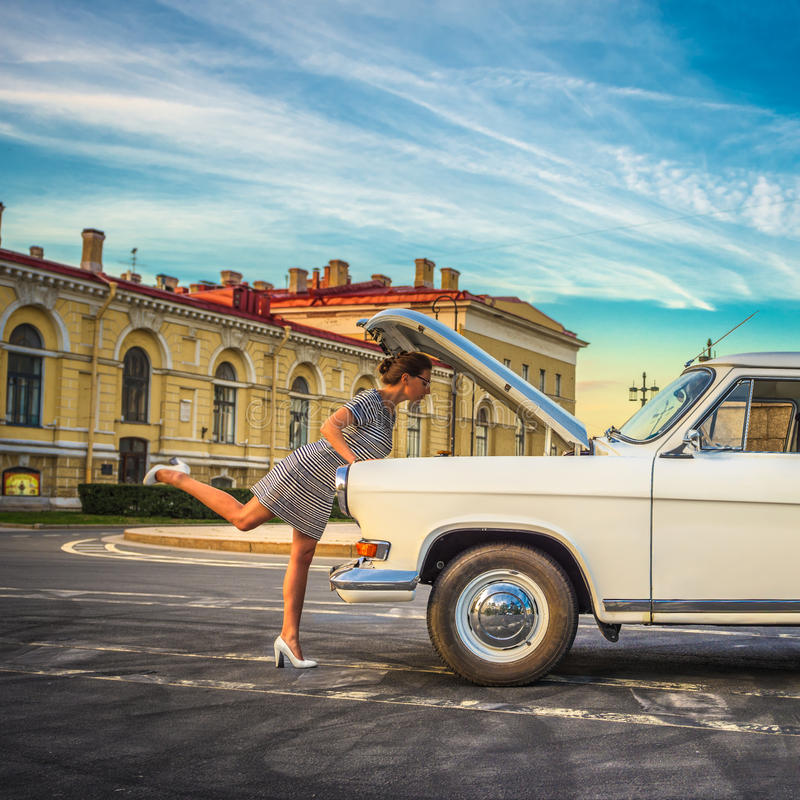 Νέα γυναίκα που επισκευάζει το αναδρομικό αυτοκίνητο στοκ εικόνες