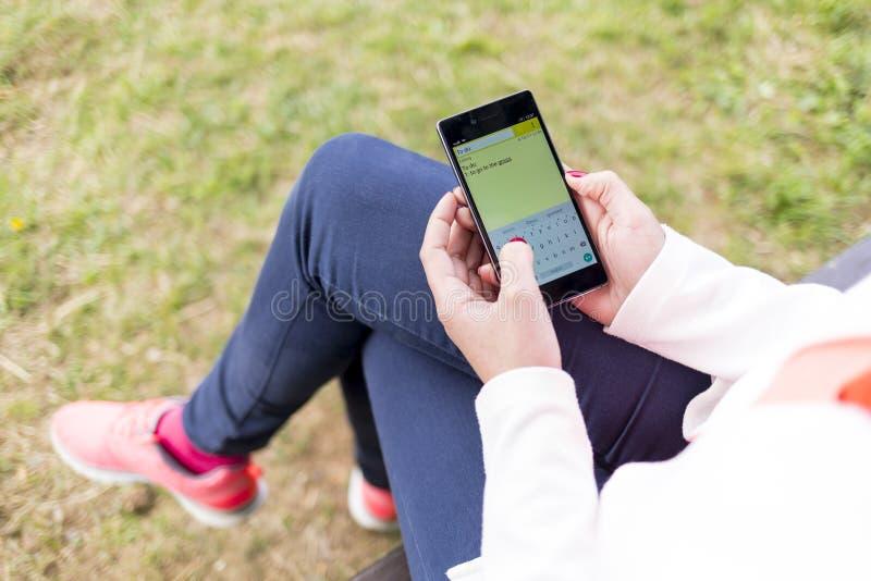 Νέα γυναίκα που εργάζεται με το smartphone στο πάρκο στοκ φωτογραφίες