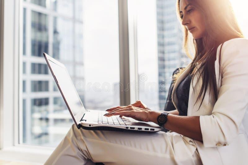 Νέα γυναίκα που εργάζεται στη συνεδρίαση lap-top στο σπίτι στοκ φωτογραφία
