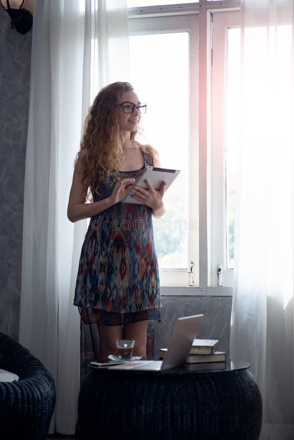 Νέα γυναίκα που εργάζεται στον ψηφιακό υπολογιστή ταμπλετών στο σπίτι στοκ εικόνες