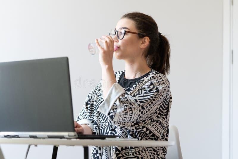 Νέα γυναίκα που εργάζεται στο lap-top και το πόσιμο νερό στα σύγχρονα διαμερίσματα στοκ φωτογραφία