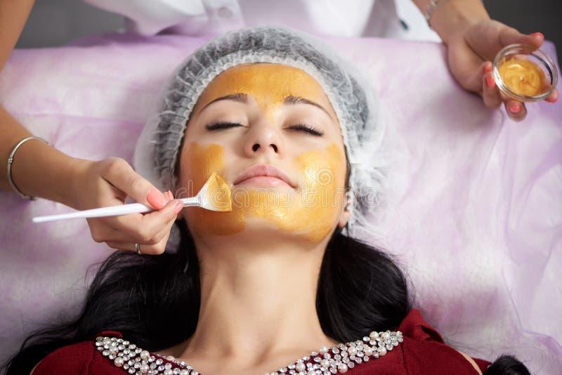 Νέα γυναίκα που εφαρμόζει την του προσώπου χρυσή μάσκα Κινηματογράφηση σε πρώτο πλάνο στοκ εικόνα με δικαίωμα ελεύθερης χρήσης