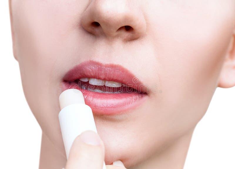 Νέα γυναίκα που εφαρμόζει το βάλσαμο στα χείλια Έννοια χειλικής προσοχής στοκ φωτογραφία