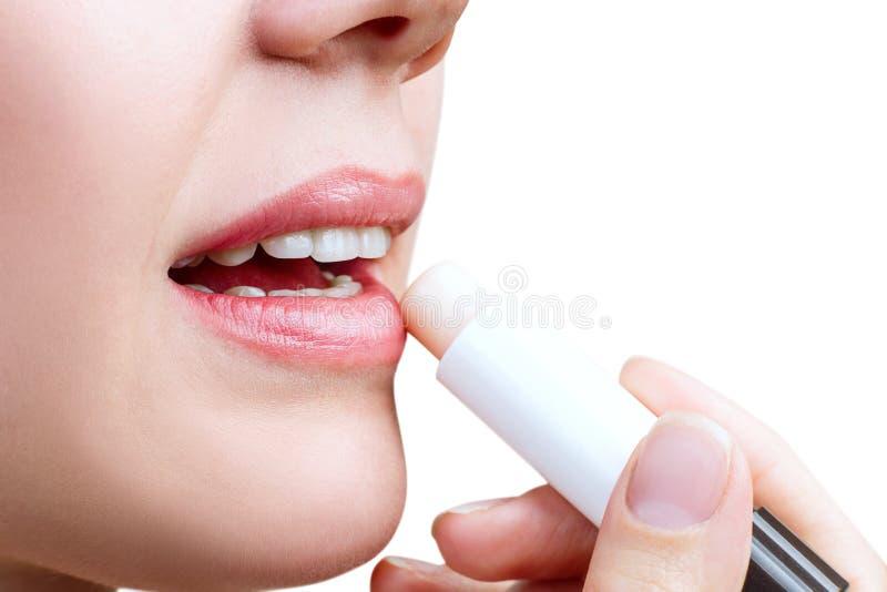 Νέα γυναίκα που εφαρμόζει το βάλσαμο στα χείλια στοκ εικόνες