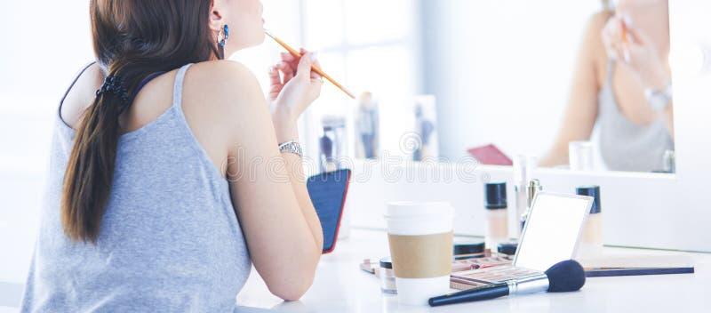 Νέα γυναίκα που εφαρμόζει το κραγιόν μπροστά από έναν καθρέφτη στοκ φωτογραφία με δικαίωμα ελεύθερης χρήσης