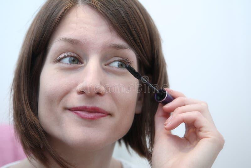 Νέα γυναίκα που εφαρμόζει mascara μπροστά από έναν καθρέφτη στοκ εικόνες