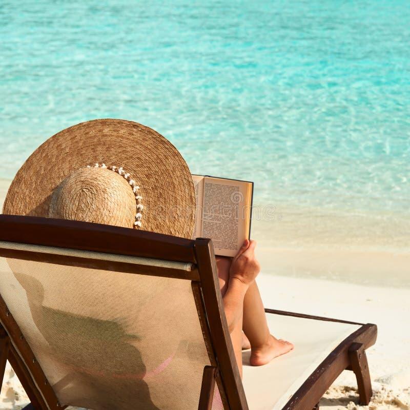 Νέα γυναίκα που διαβάζει ένα βιβλίο στην παραλία στοκ φωτογραφία