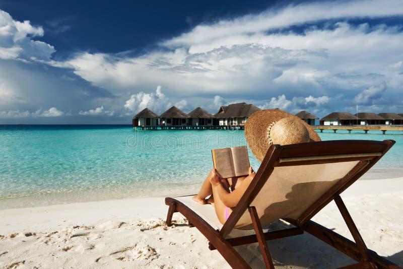 Νέα γυναίκα που διαβάζει ένα βιβλίο στην παραλία στοκ εικόνες με δικαίωμα ελεύθερης χρήσης