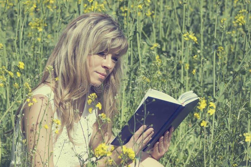 Νέα γυναίκα που διαβάζει ένα βιβλίο στο λιβάδι βιασμών στοκ φωτογραφία με δικαίωμα ελεύθερης χρήσης