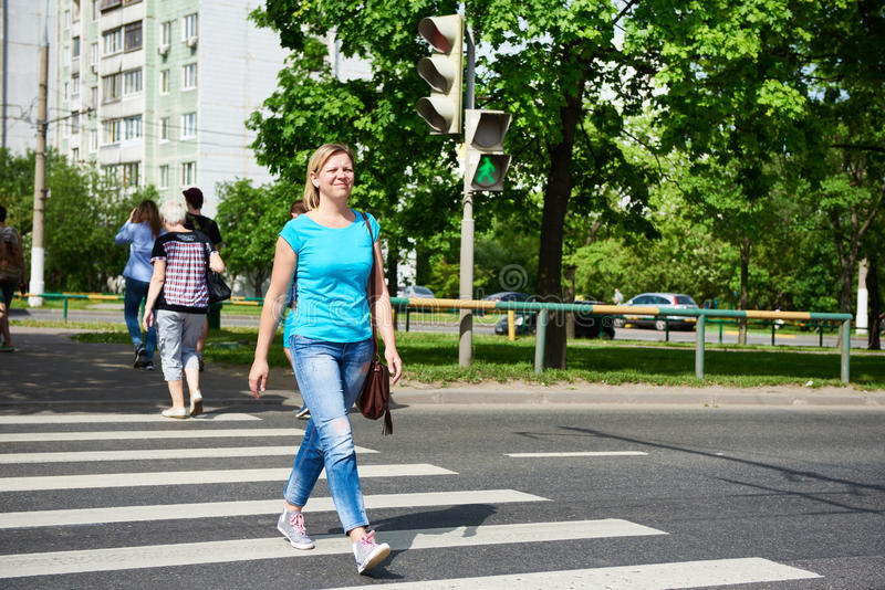 Νέα γυναίκα που διασχίζει το δρόμο στο πράσινο φως στοκ φωτογραφία με δικαίωμα ελεύθερης χρήσης