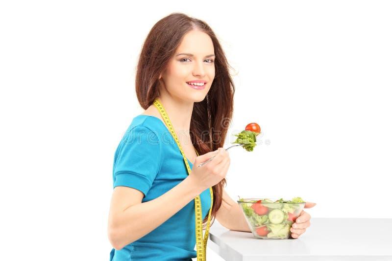 Νέα γυναίκα που κάθεται και που τρώει μια φρέσκια σαλάτα στοκ εικόνες με δικαίωμα ελεύθερης χρήσης