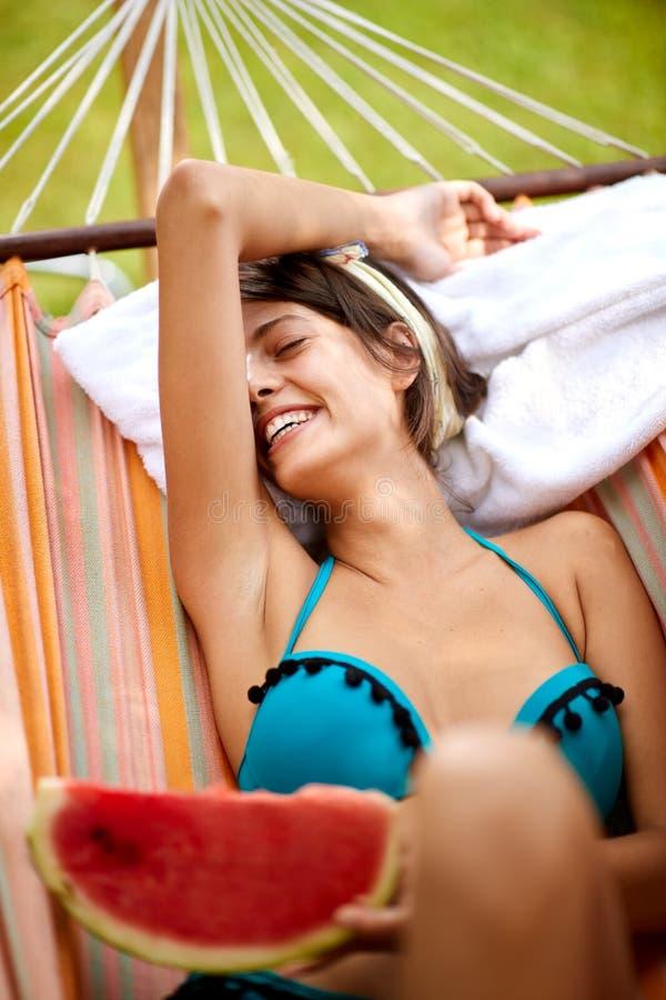 Νέα γυναίκα που κάνει ηλιοθεραπεία στην αιώρα στοκ εικόνα με δικαίωμα ελεύθερης χρήσης
