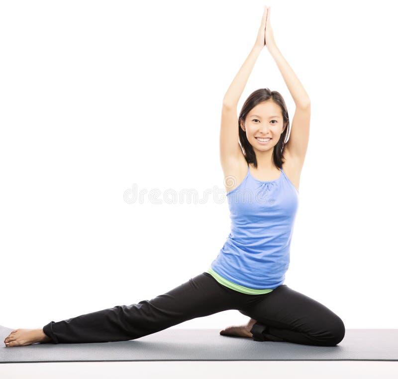 Νέα γυναίκα που κάνει την άσκηση γιόγκας στο χαλί στοκ φωτογραφία