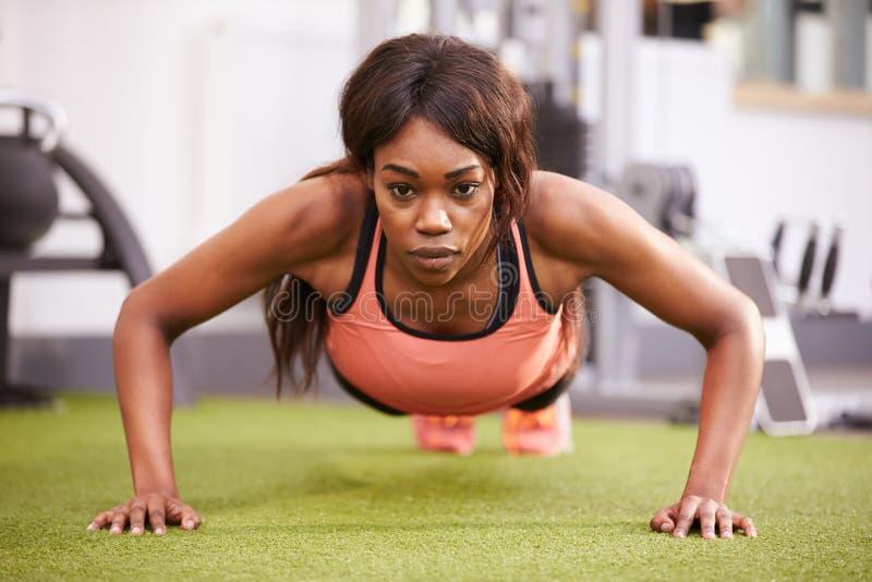 Νέα γυναίκα που κάνει την ώθηση UPS σε μια γυμναστική στοκ φωτογραφίες με δικαίωμα ελεύθερης χρήσης