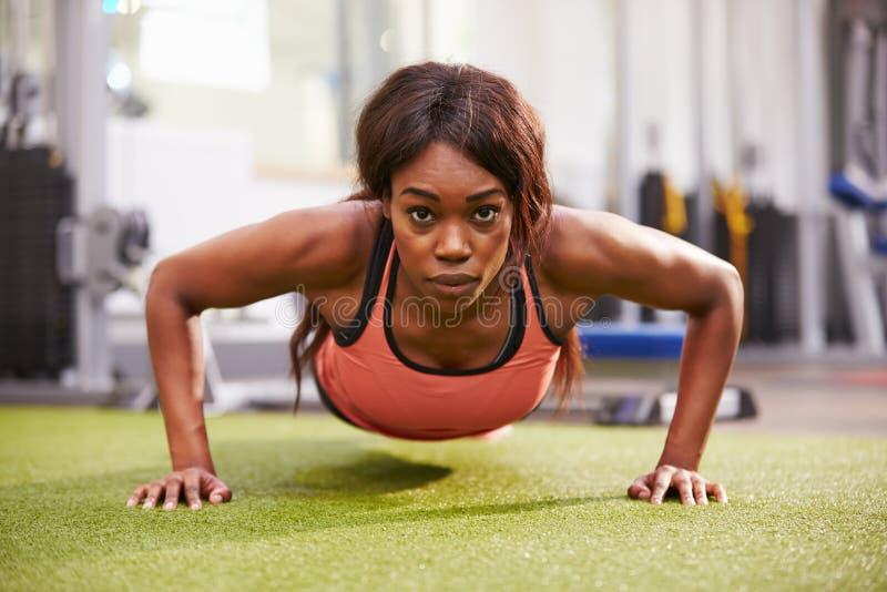 Νέα γυναίκα που κάνει την ώθηση UPS σε μια γυμναστική στοκ εικόνες με δικαίωμα ελεύθερης χρήσης