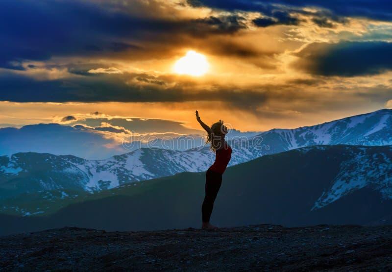 Νέα γυναίκα που κάνει τη γιόγκα στα βουνά στοκ εικόνες