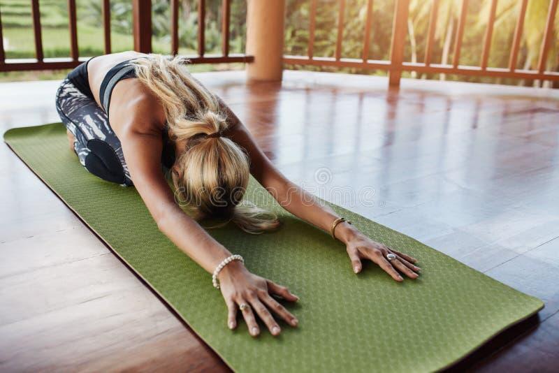 Νέα γυναίκα που κάνει τη γιόγκα στο χαλί άσκησης στοκ φωτογραφίες