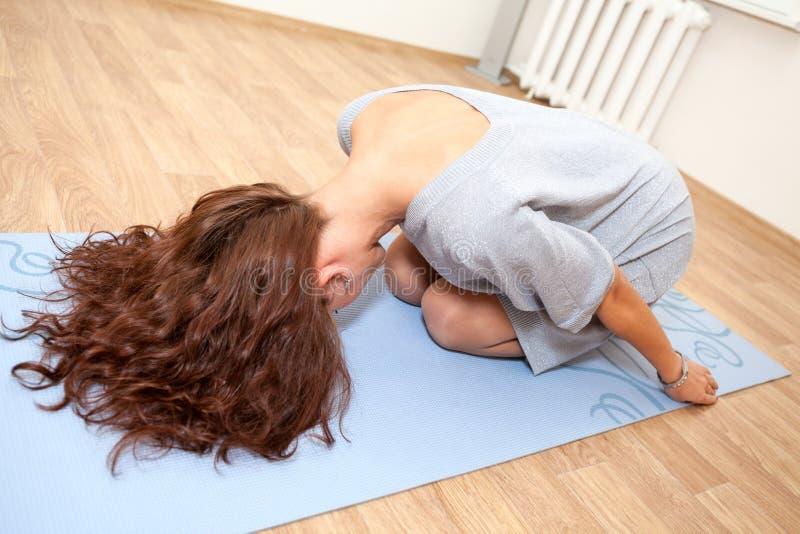 Νέα γυναίκα που κάνει τις αεροβικές ασκήσεις που κάθονται στο χαλί στοκ εικόνες