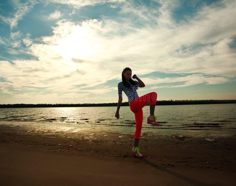 Νέα γυναίκα που κάνει τις ασκήσεις ικανότητας στην παραλία άμμου στοκ εικόνες