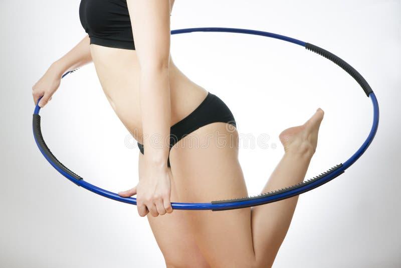 Νέα γυναίκα που κάνει τις ασκήσεις με τη στεφάνη στοκ εικόνες με δικαίωμα ελεύθερης χρήσης