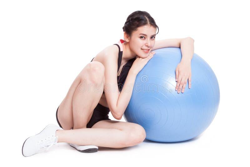 Νέα γυναίκα που κάνει τις ασκήσεις με τη σφαίρα ικανότητας στοκ φωτογραφίες