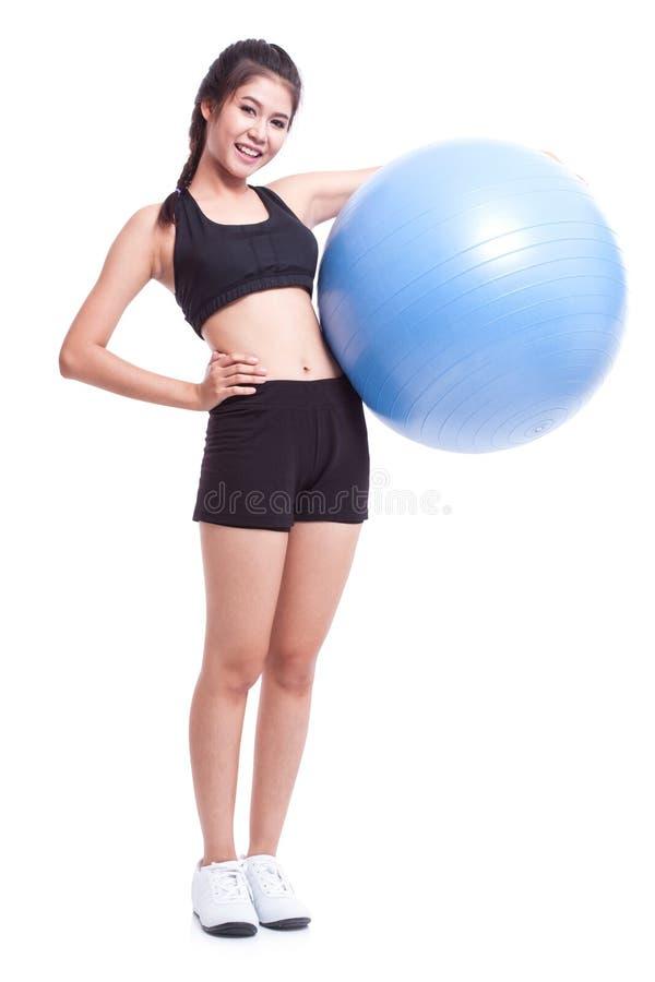 Νέα γυναίκα που κάνει τις ασκήσεις με τη σφαίρα ικανότητας στοκ εικόνα