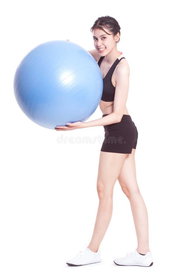 Νέα γυναίκα που κάνει τις ασκήσεις με τη σφαίρα ικανότητας στοκ φωτογραφία