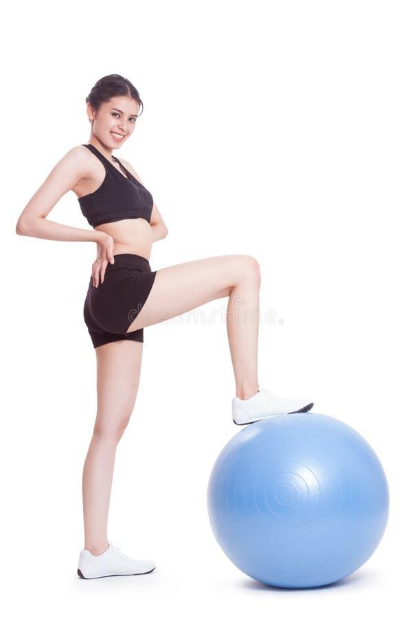 Νέα γυναίκα που κάνει τις ασκήσεις με τη σφαίρα ικανότητας στοκ εικόνα με δικαίωμα ελεύθερης χρήσης