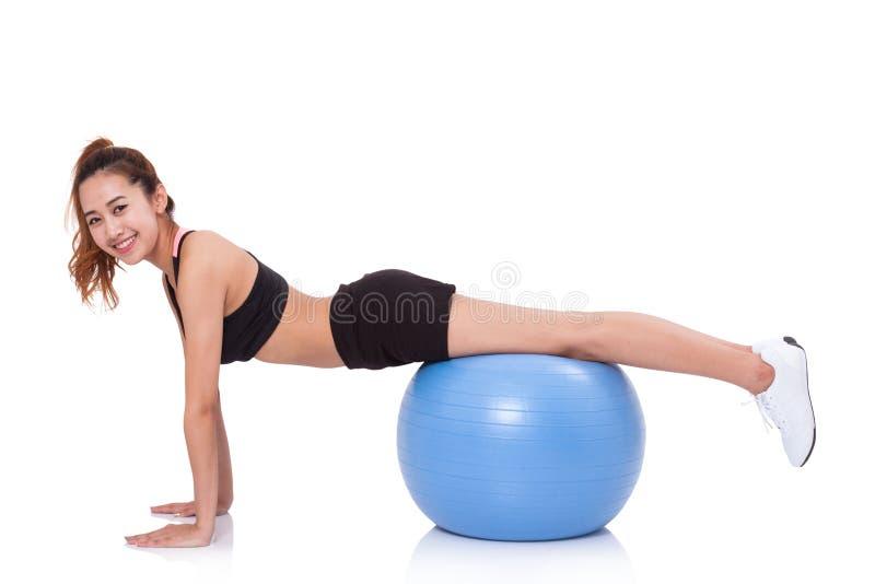 Νέα γυναίκα που κάνει τις ασκήσεις με τη σφαίρα ικανότητας στοκ εικόνες