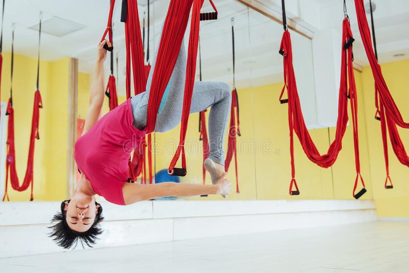 Νέα γυναίκα που κάνει τις ενάντιες στη βαρύτητα ασκήσεις γιόγκας στοκ φωτογραφία με δικαίωμα ελεύθερης χρήσης