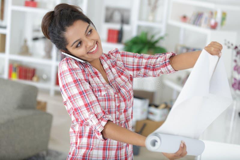 Νέα γυναίκα που κάνει τις επισκευές διαμερισμάτων στον τοίχο στοκ φωτογραφία με δικαίωμα ελεύθερης χρήσης