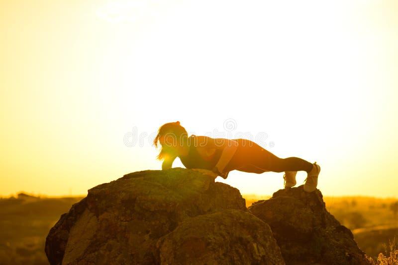 Νέα γυναίκα που κάνει το ώθηση-UPS στα βουνά Άσκηση Workout στο ηλιοβασίλεμα r στοκ φωτογραφίες