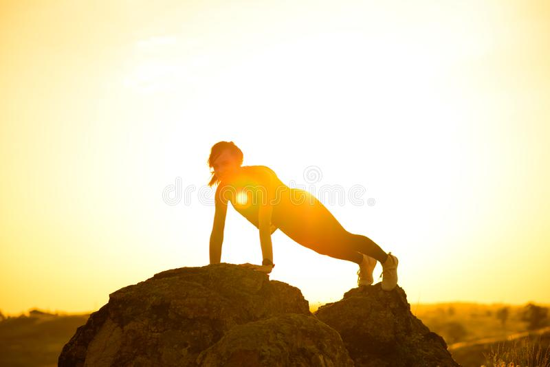 Νέα γυναίκα που κάνει το ώθηση-UPS στα βουνά Άσκηση Workout στο ηλιοβασίλεμα r στοκ εικόνα με δικαίωμα ελεύθερης χρήσης